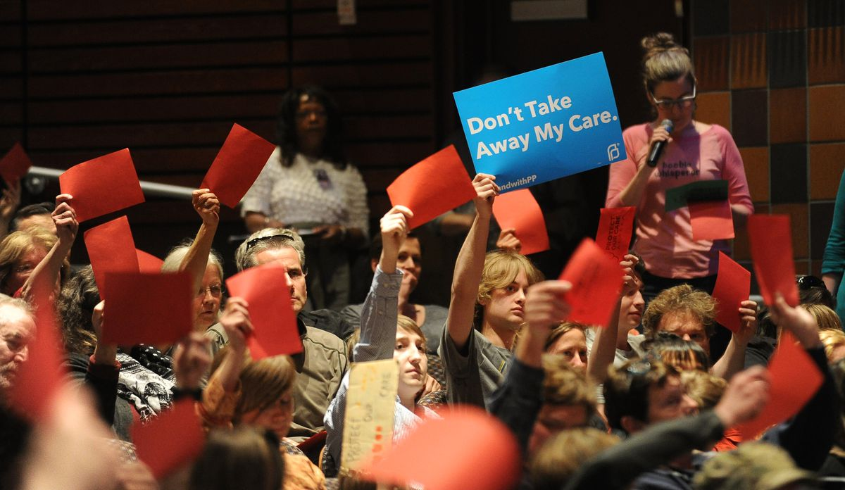 Red cards, signaling disapproval, go up as Republican U.S. Sen. Dan Sullivan answers a question about the GOP health care bill at a town hall meeting he held at Bartlett High School in Anchorage on Saturday. (Bob Hallinen / Alaska Dispatch News)