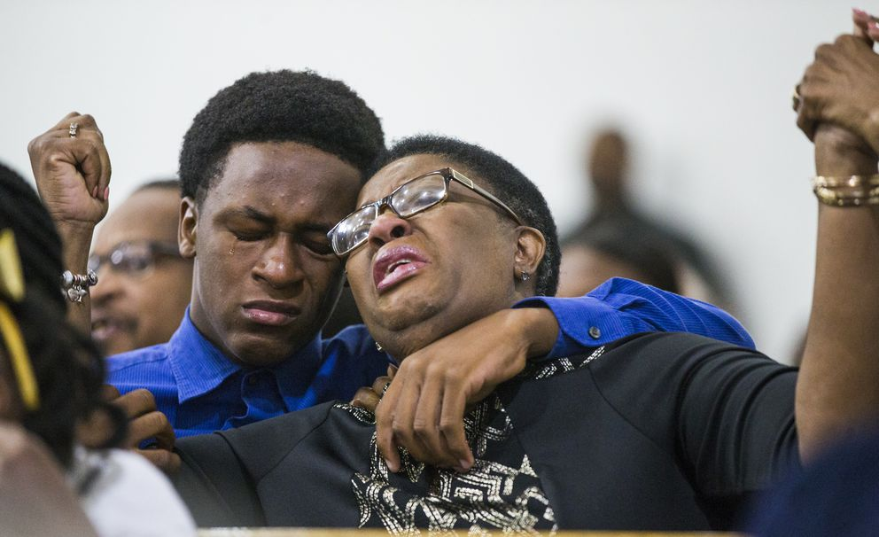 Allison Jean raises her hands in the air as she leans on her son, Grant, 15, during a prayer service for her son and Grant's brother Botham Jean at the Dallas West Church of Christ on Sunday, Sept. 9, 2018 in Dallas. Botham Jean was shot and killed by Dallas police officer Amber Guyger in his apartment on Thursday night. (Shaban Athuman/The Dallas Morning News via AP)
