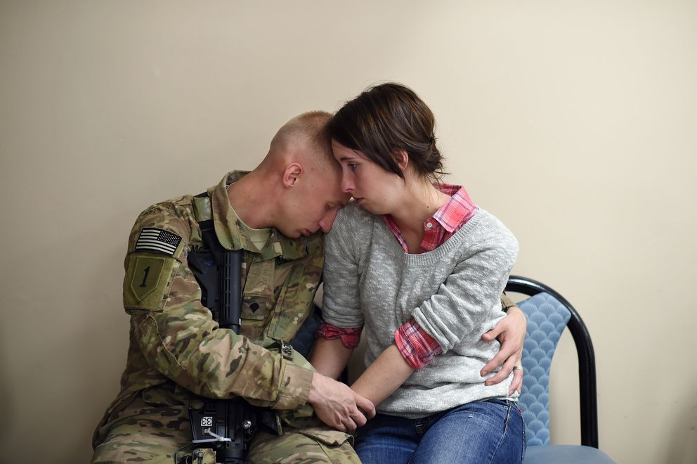 SPC Caleb McKinnon embraces his wife, Savannah McKinnon, as he and others prepare to be deployed to Afghanistan from Fort Campbell, Ky., on Nov. 9, 2014. (Washington Post photo by Matt McClain)