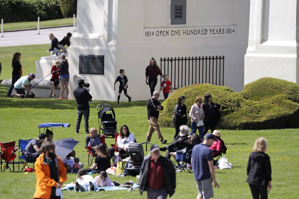 In this photo taken May 17, 2020, people picnic, play and walk back and forth across the border between the U.S. and Canada in Peace Arch Park. (AP Photo/Elaine Thompson)