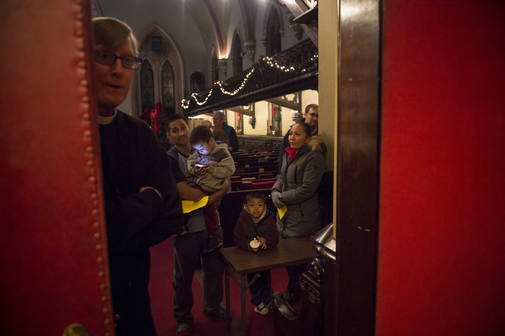 Javier Flores Garcia, who entered the U.S. illegally from Mexico; his family; and the Rev. Robin Hynicka, the pastor of Arch Street United Methodist Church, wait for the start of a Christmastime ritual in downtown Philadelphia, Dec. 16. Providing sanctuary from deportation efforts is shaping up as a priority of the religious left across various faiths and ethnicities. (Charles Mostoller/The New York Times)