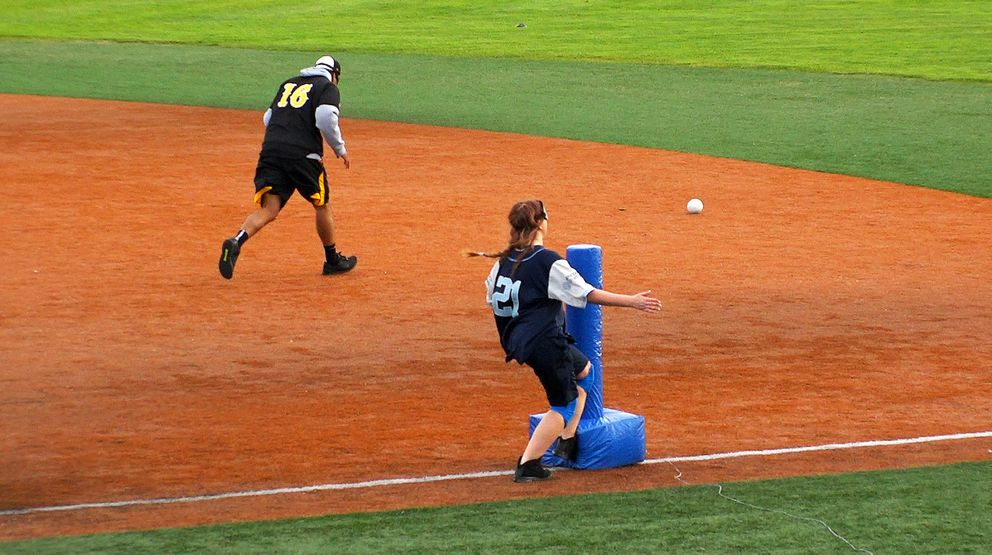 Seattle Sluggers Abby Schmidt scores a run by tagging first base before Bryant Harris of the Anchorage Bucs can field the beep baseball. (Scott Jensen / Alaska Dispatch News)