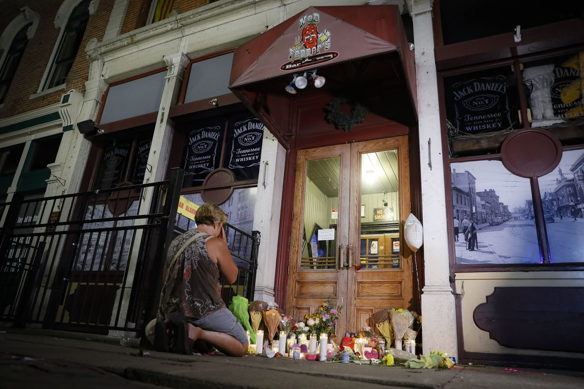 In this Aug. 4, 2019 file photo, mourners visit a makeshift memorial outside Ned Peppers bar following a vigil at the scene of a mass shooting in Dayton, Ohio. (AP Photo/John Minchillo, File)
