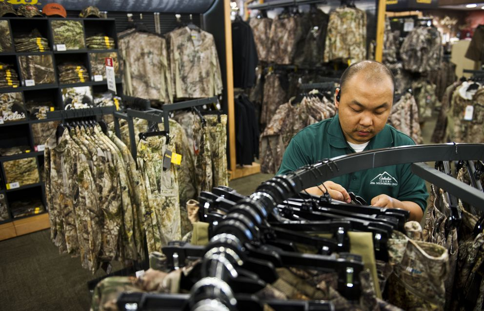 Chue Moua works in the camouflage section of the Cabela's store in South Anchorage on Friday, July 15, 2016. (Marc Lester / Alaska Dispatch News)