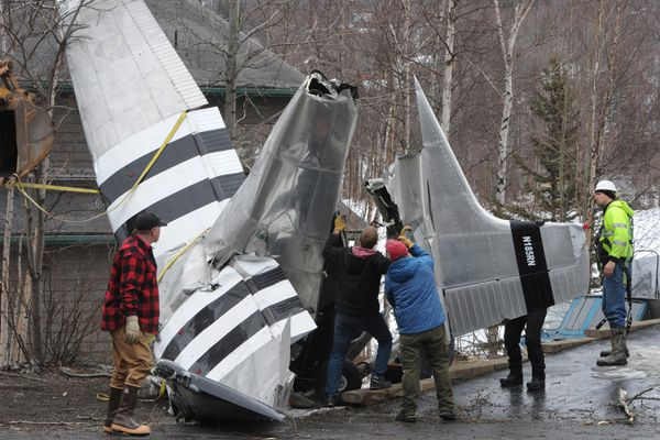 On Sunday, workers remove a Cessna 185 wheel-ski equipped airplane that crashed while landing at Fire Lake on Saturday evening, April 11, 2020. Four people were injured in the crash. (Bill Roth / ADN)