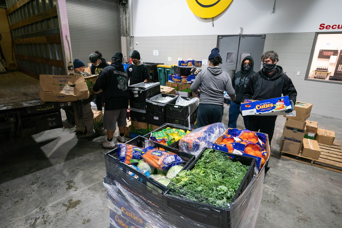Bean's Cafe staff sort and load fresh produce salvaged from an overturned truck on Saturday, Dec. 26, 2020 at the Dena'ina Civic and Convention Center in Anchorage. The fresh produce will help sustain operations at the soup kitchen for several months, according to executive director Lisa Sauder. (Loren Holmes / ADN)