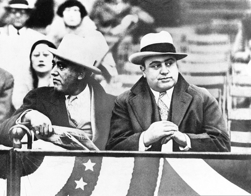 FILE - In this Oct. 10, 1931, file photo Al Capone, Chicago gangland, right, attends a game between Notre Dame and Northwestern Grid in Chicago. Former Alderman A.J. Prignano is on the left. Capone earned tens of millions of dollars annually from bootlegging and speakeasies. (AP Photo, File)