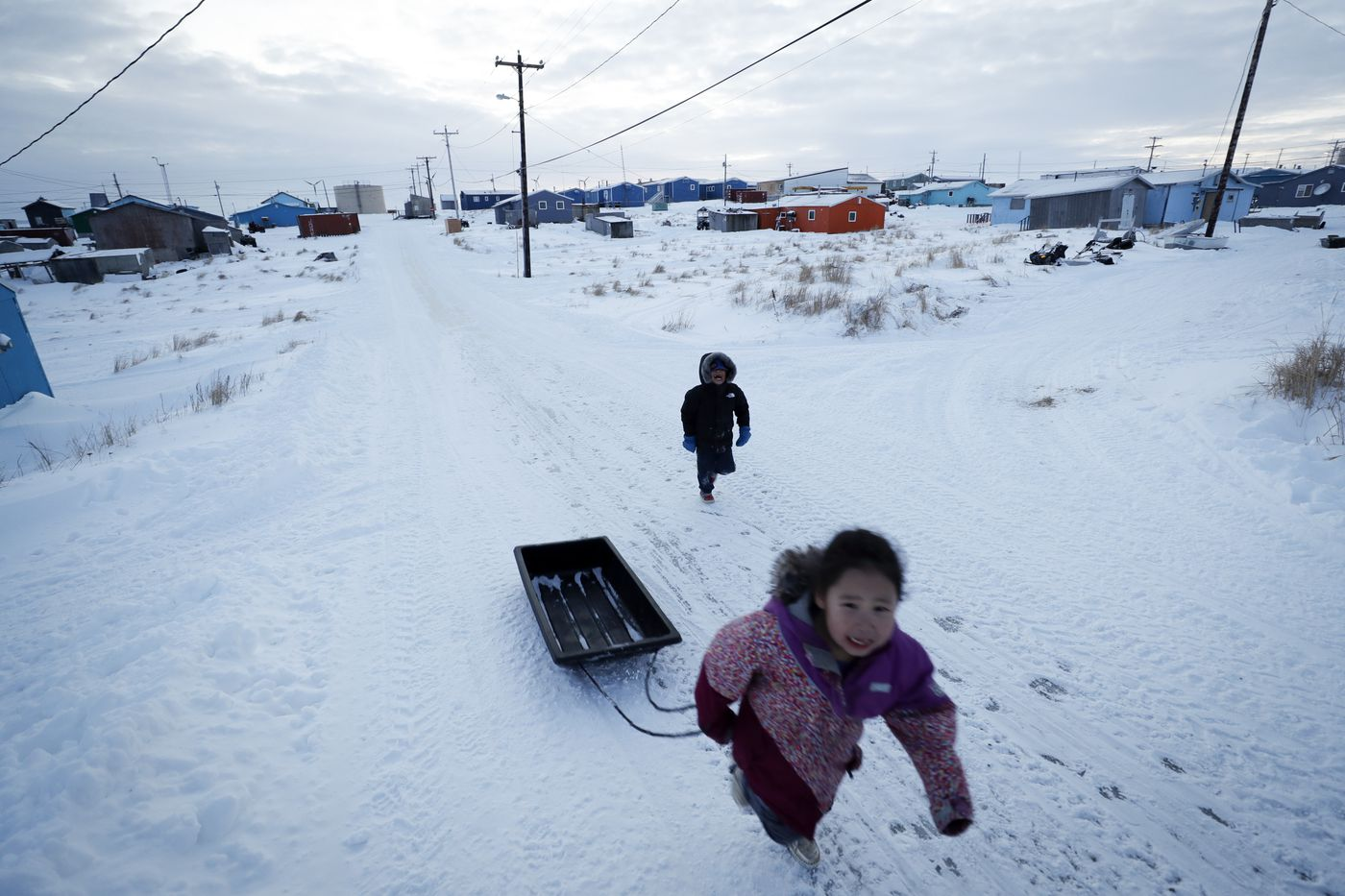 Children play in the snow Saturday, Jan. 18, 2020, in Toksook Bay, Alaska. The first Americans to be counted in the 2020 Census starting Tuesday, Jan. 21, live in this Bering Sea coastal village. The Census traditionally begins earlier in Alaska than the rest of the nation because frozen ground allows easier access for Census workers, and rural Alaska will scatter with the spring thaw to traditional hunting and fishing grounds. (AP Photo/Gregory Bull)