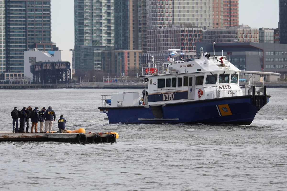 National Transportation Safety Board investigators on Monday at the scene of the wreckage of a chartered helicopter that crashed Sunday into the East River as it sits submerged under yellow flotationmarkers in New York. REUTERS/Shannon Stapleton