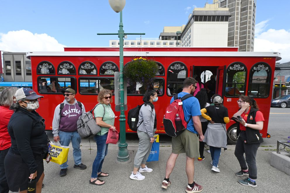 Kelly Priest, his wife Barbie, their son Robert and Robert's girlfriend Alba Soltero, who are visiting from Texas, prepare to board an Anchorage Trolley Tours on Fourth Avenue in downtown on Thursday, June 17, 2021. (Bill Roth / ADN)
