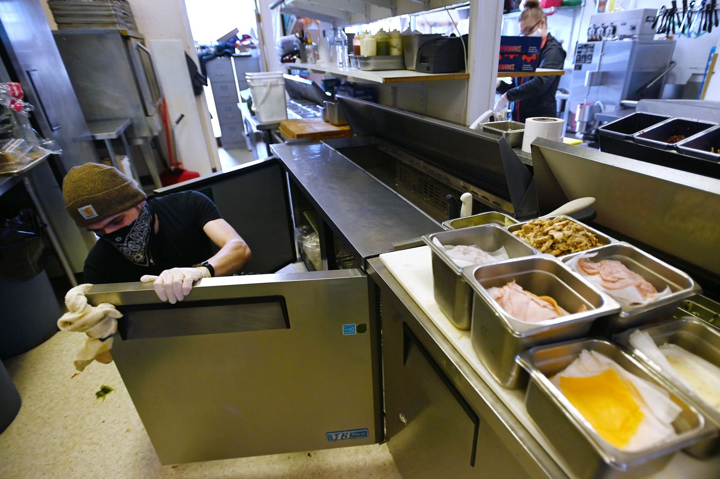 Caleb Davidson sanitizes refrigerator doors before storing lunch meat at Sis's Café and Catering on Old Seward Highway on Monday, April 6, 2020. (Bill Roth / ADN)