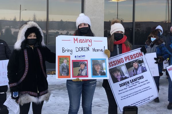 Doren Sanford's family members hold signs with information about the 35-year-old, who's been missing since Aug. 28 while speaking to the gathered crowd in Fairbanks, Jan. 23, 2021. Sam Ferrara/News-Miner