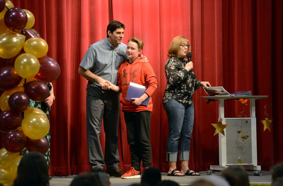 Kohl Russell's teacher Todd Dietsch, left, and Principal Cindy Hemry, right, greet Kohl and classmates as they cross the stage to receive certificates and graduation photos during the 6th Grade Moving-Up Ceremony on Tuesday morning May 22, 2019, at Gladys Wood Elementary School. (Erik Hill)