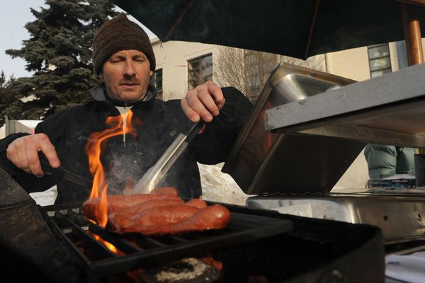 Michael Anderson opened his M.A.s Gourmet Dogs cart in front of the old federal building in downtown Anchorage on Friday, March 23, 2012. It is the first day of the season for and many West High students were on hand ordering reindeer sausage and other hot dogs. (BOB HALLINEN / ADN archive 2012)