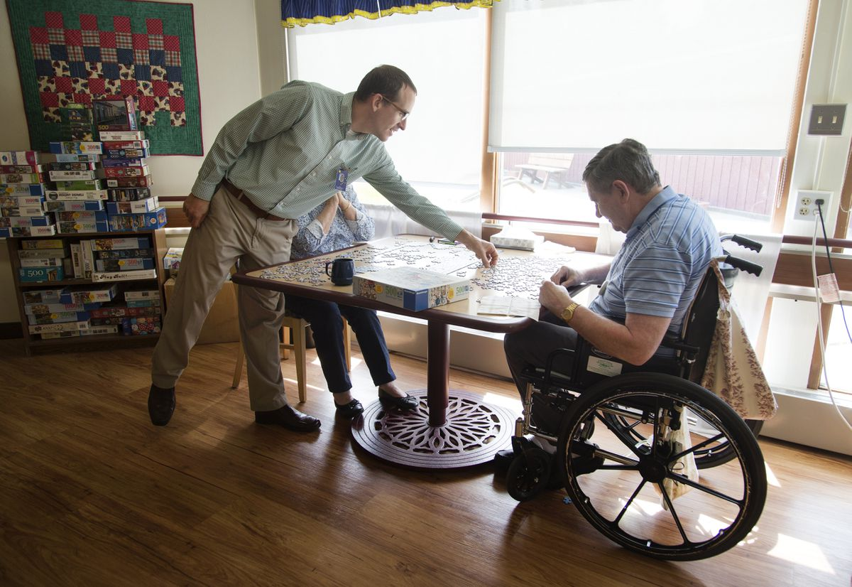 Joshua Shaver, the Alaska Veterans and Pioneers Home administrator, helps Larry Stadem with a puzzle on June 8, 2017, at the Alaska Veterans and Pioneers Home in Palmer. (Rugile Kaladyte / Alaska Dispatch News)