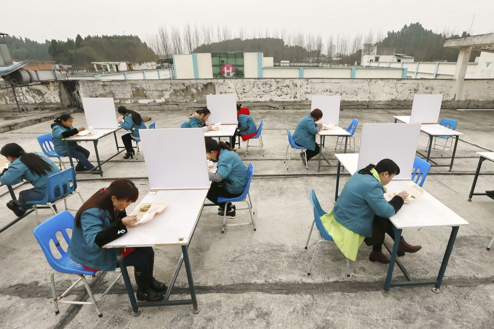 In this Friday, Feb. 14, 2020, photo, factory workers are separated by partitions as a precaution against infection as they take their lunch break on the roof of an electronics factory in Suining in southwestern China's Sichuan Province. (Chinatopix via AP)