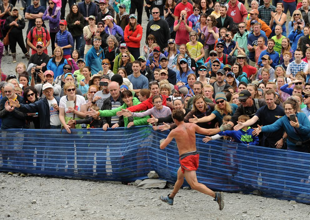 A runner collects high-fives from the crowd at the base of Seward's Mount Marathon in 2016. (Bob Hallinen / ADN archive)