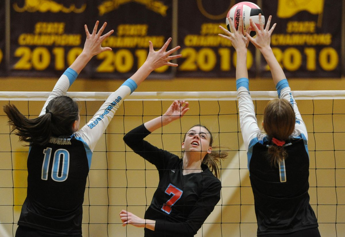 East's Avery Northcutt (7) hits the ball against Chugiak blockers Aubre Adams (10) and Sara Moore (1) in first-round acton Tuesday at the CIC volleyball tournament. (Bill Roth / ADN)