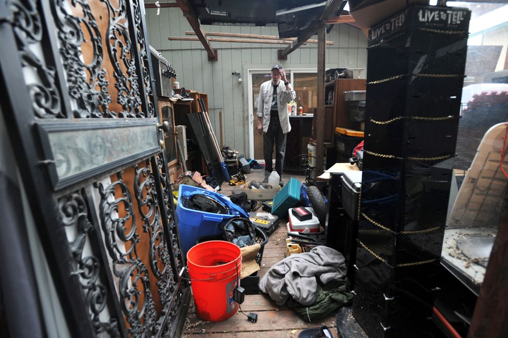 The back deck of the home is filled with furniture and a wide assortment of items ranging from an aquarium to rusting power tools. (Erik Hill / Alaska Dispatch News)