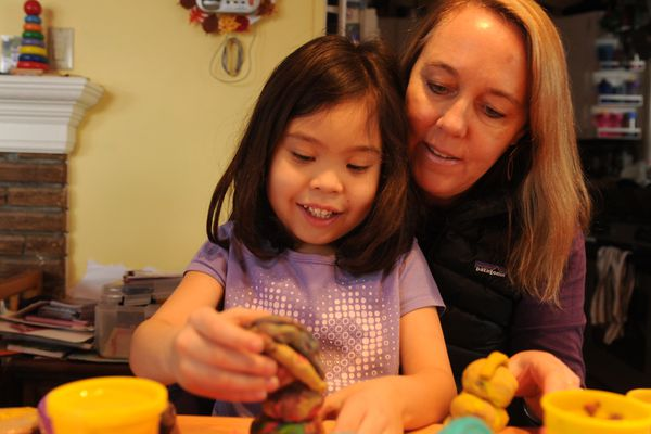Olive Reed and her mother Paula Dobbyn play with Play-Doh at home in Anchorage, AK on Friday, February 20, 2015. Olive Reed is the adopted daughter of Paula Dobbyn and John Reed.