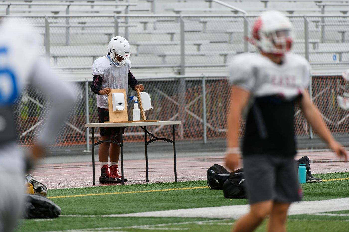 An East High School player sets hand sanitizer out during practice on September 2, 2020. (Marc Lester / ADN)