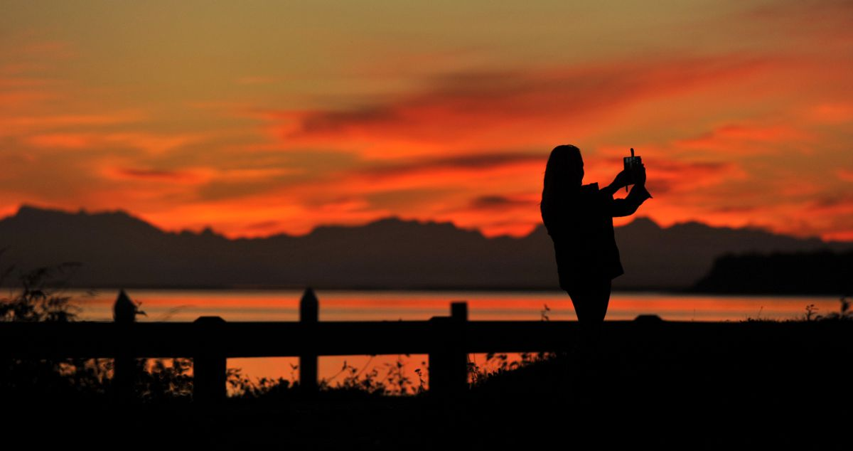 Carla Hayes photographs the sunset at the Small Boat Launch neat the Port of Anchorage in Anchorage, Alaska, on Tuesday, September 13, 2016. Anchorage daylight is vanishing day by day, until winter solstice, when we'll see about 5 1/2 hours. (Bob Hallinen / Alaska Dispatch News)