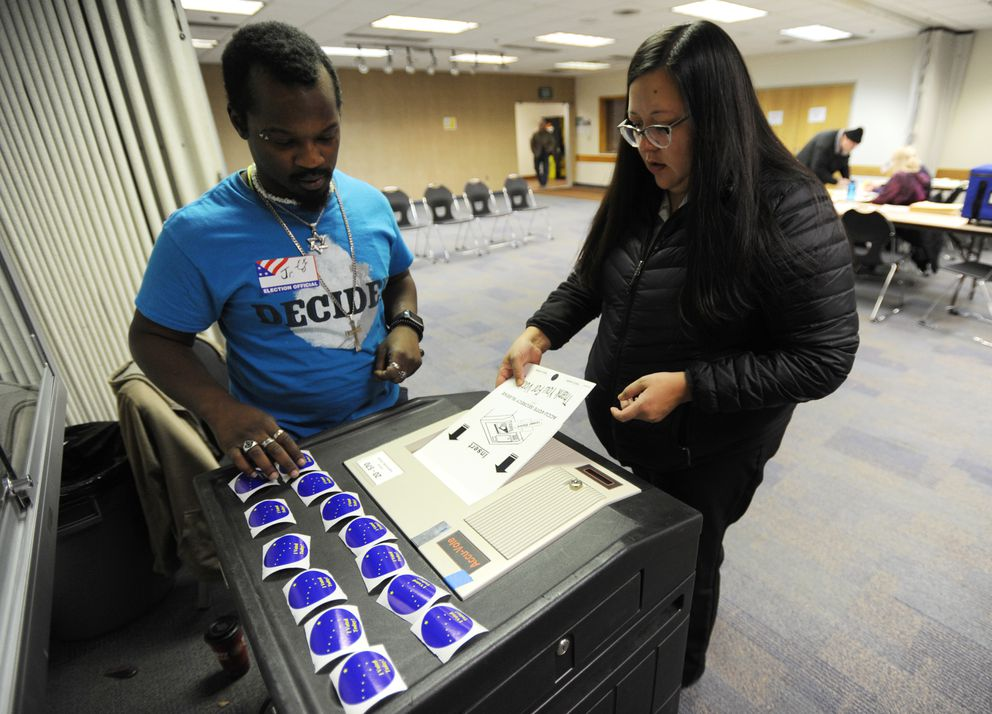 "Election official Cavartus Oliver, Jr. reaches for am ""I Voted"" sticker as Tia Lewis casts her ballot at the Fairview Community Recreation Center on Election Day, Tuesday, Nov. 6, 2018. (Bill Roth / ADN)"