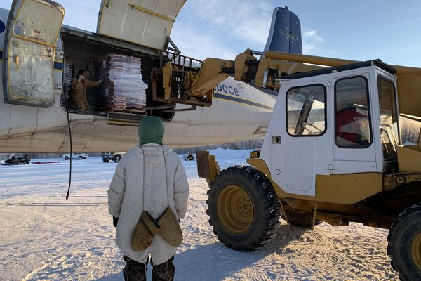 A donation of 39,000 pounds of dog food from Purina arrives in Tanana in November 2020 to help feed mushing teams through the winter. Many mushers rely on chum salmon to feed their dog teams all winter, but they were cut off from subsistence fishing this year due to poor salmon runs. (Courtney Agnes)