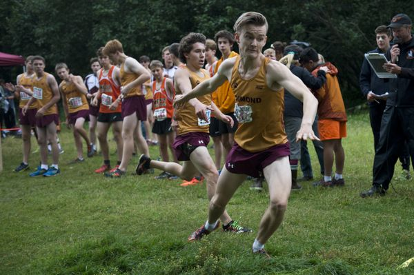 Niko Latva-Kiskola, right, is tagged by his Dimond teammate Fred Rygh. Their four-person relay team won the steel bucket trophy for the boys race. West and Dimond cross country running teams ran relay races for the painted steel bucket trophy, an annual tradition between the schools, at Kincaid Park on August 14, 2018. (Marc Lester / ADN)