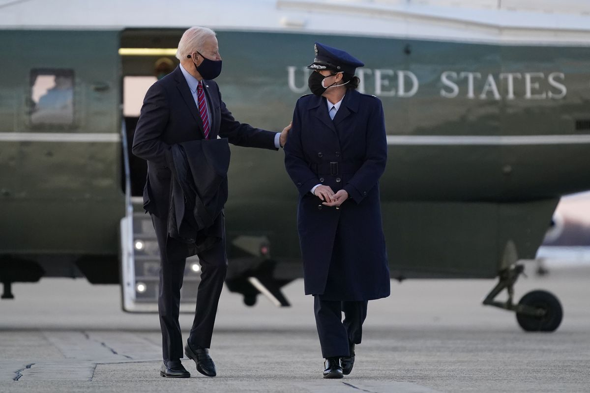 President Joe Biden speaks with a member of the U.S. Air Force after handing her a challenge coin as he walks to Air Force One at Andrews Air Force Base, Md., Friday, Feb. 5, 2021. (AP Photo/Patrick Semansky)