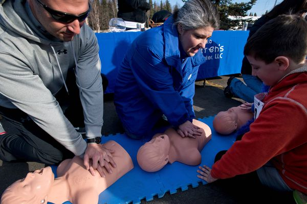 Kitty Wellman, center, of the Alaska Children's Heart Center, demonstrates CPR compressions Saturday. Jim Dennis is at left and his son Matthew, 9, is at right. About 5,000 runners and walkers participated in the 2013 Alaska Heart Run on Saturday, April 27, 2013. The event is a fundraiser for the American Heart Association. (Marc Lester / Alaska Dispatch News)