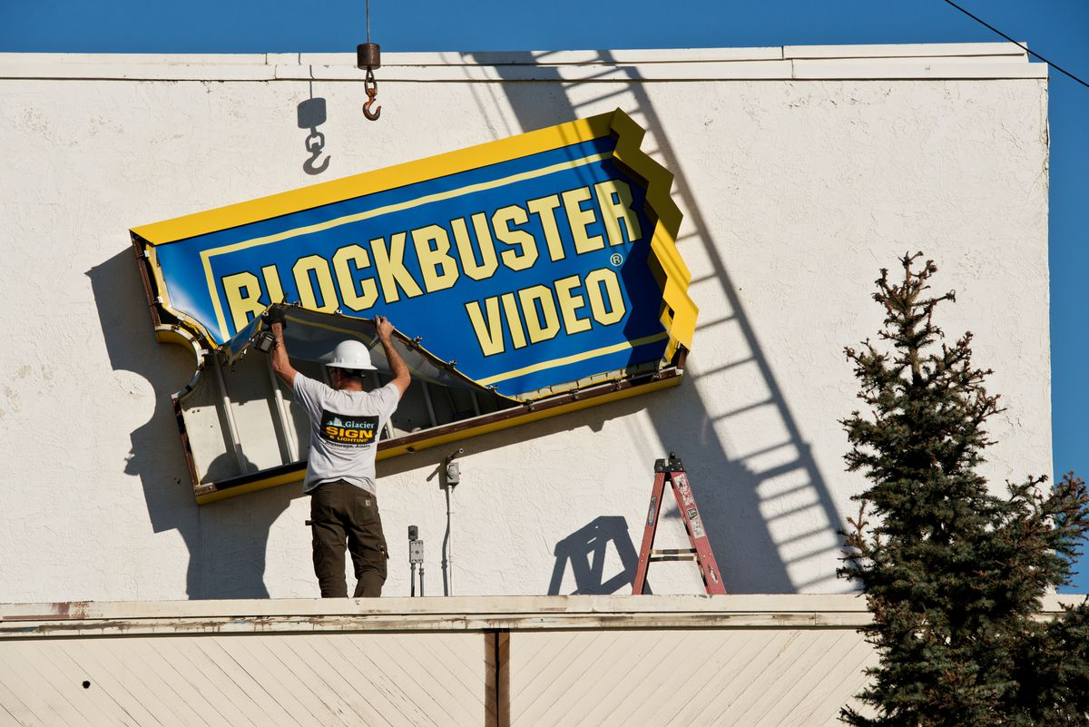 Jason Eccles, of Glacier Sign and Lighting, removes a Blockbuster Video sign from the rear of the former Northern Lights Boulevard location in Midtown Anchorage, which closed in late 2016. (Marc Lester / Alaska Dispatch News)