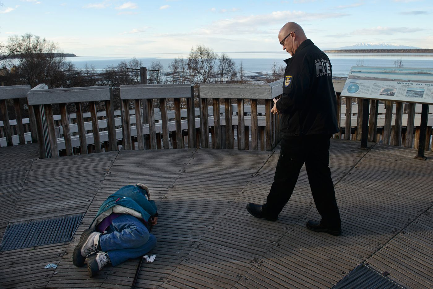 Anchorage Fire Deparment Battalion Chief Mike Crotty approaches a woman laying on the deck beneath a statue of Captain Cook in downtown Anchorage. Crotty, who supervises medics on the AFD staff, talked to a Downtown Security Ambassador to arrange for the woman o be transported by Anchorage Safety Patrol. Photographed on Saturday, November 8, 2014. Marc Lester / ADN