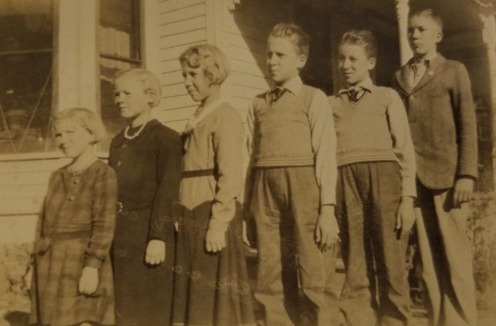 In this undated photo, provided by family member Susan Lawrence on Wednesday, June 13, 2018, the Pieper children, from left, MaryAnn, Leona, Ivona, twins Ludwig and Julius and Fred stand outside the family home in Nebraska. For decades, he had a number for a name, Unknown X-9352, at a World War II American cemetery in Belgium where he was interred. On Tuesday, June 19, 2018, Julius Pieper will be reunited with his twin brother in Normandy, where the two Navy men died together when their ship shattered on an underwater mine while trying to reach the blood-soaked D-Day beaches. (Susan Lawrence via AP)