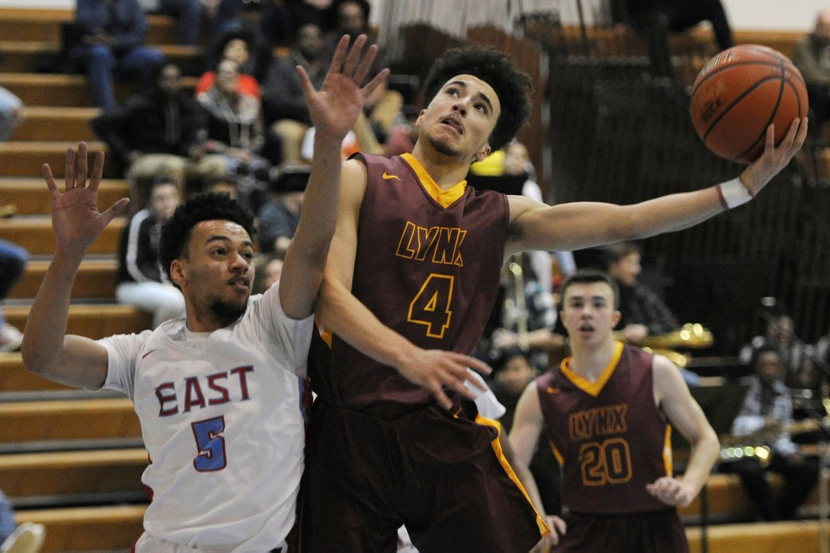 East High senior Kaeleb Johnson defends as Dimond High junior Isaiah Moses drives to the basket during the Lynx 52-45 victory over the Thunderbirds. (Bill Roth/ ADN)