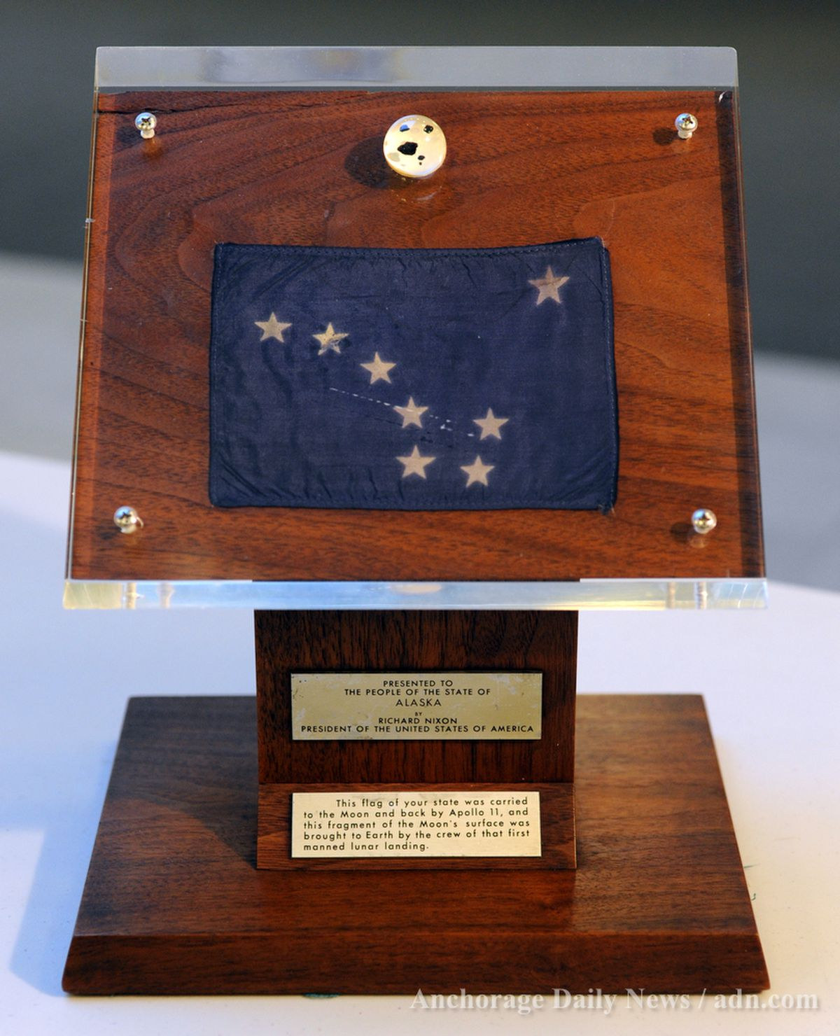 Tiny fragments of moon rock were accompanied by a state flag in the plaque presented by President Richard Nixon to Gov. Keith Miller in 1969. The plaque and rocks disappeared following a 1973 fire at the Alaska Transportation Museum in Anchorage, and were displayed again to Alaskans upon their overnight return to the state Thursday Dec. 6, 2012 at the Anchorage School District administration building.