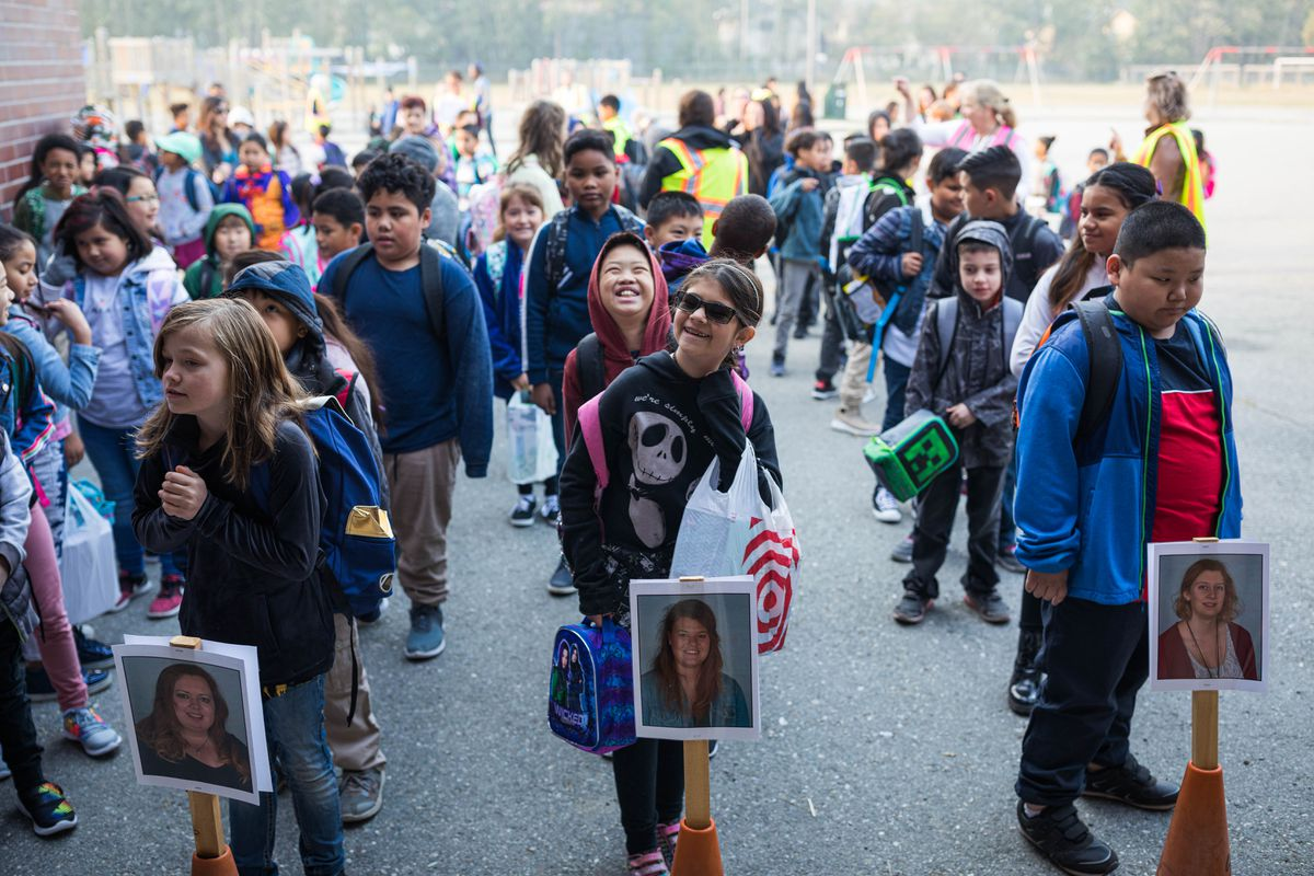 Students line up behind pictures of their teachers before the first day of school Tuesday, Aug. 20, 2019 at Muldoon Elementary. (Loren Holmes / ADN)