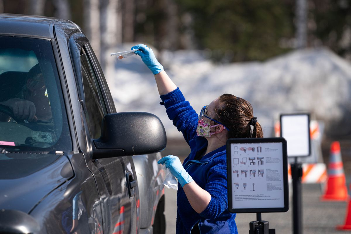 Dawn Hall, lab manager at the Sunshine Clinic in Willow, hands a nasal swab test kit to a person at a drive-through COVID-19 test site at Su Valley Junior/Senior High School in Talkeetna on Thursday, April 30, 2020. (Loren Holmes / ADN)
