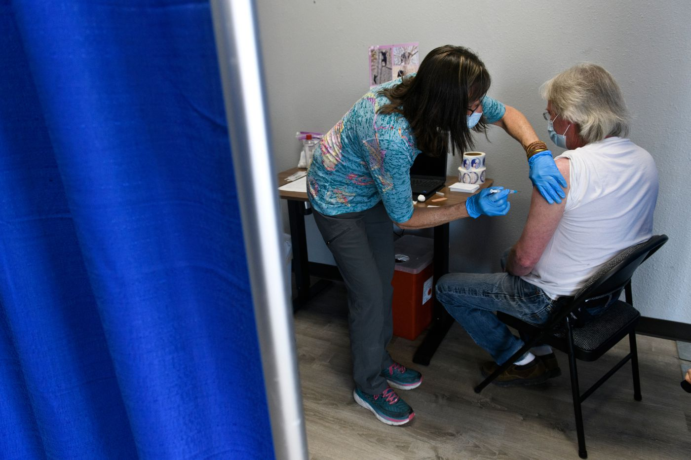 """Kevin Kowalkowski, right, gets a COVID-19 vaccine shot at the Soldotna walk-in clinic on May 26, 2021. """"I got my yard work done and my wife kept bugging me,"""" Kowalski said about why he decided to come in. (Marc Lester / ADN)"""