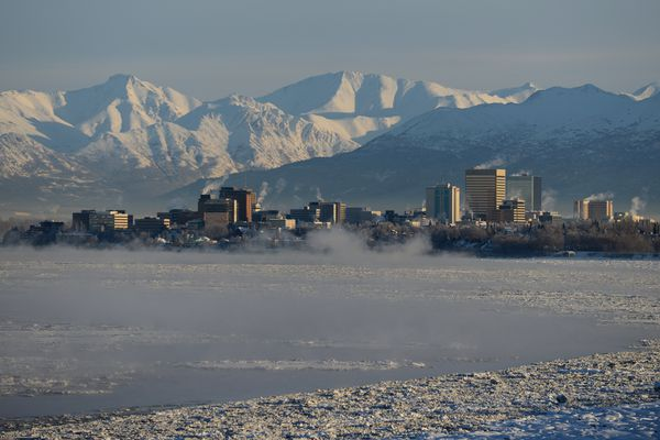 Steam rises from buildings and fog rises off Cook Inlet on a cold morning in downtown Anchorage, Alaska on Wednesday, January 18, 2017. The snow covered Chugach Mountains rise in the background. (Bob Hallinen / Alaska Dispatch News)