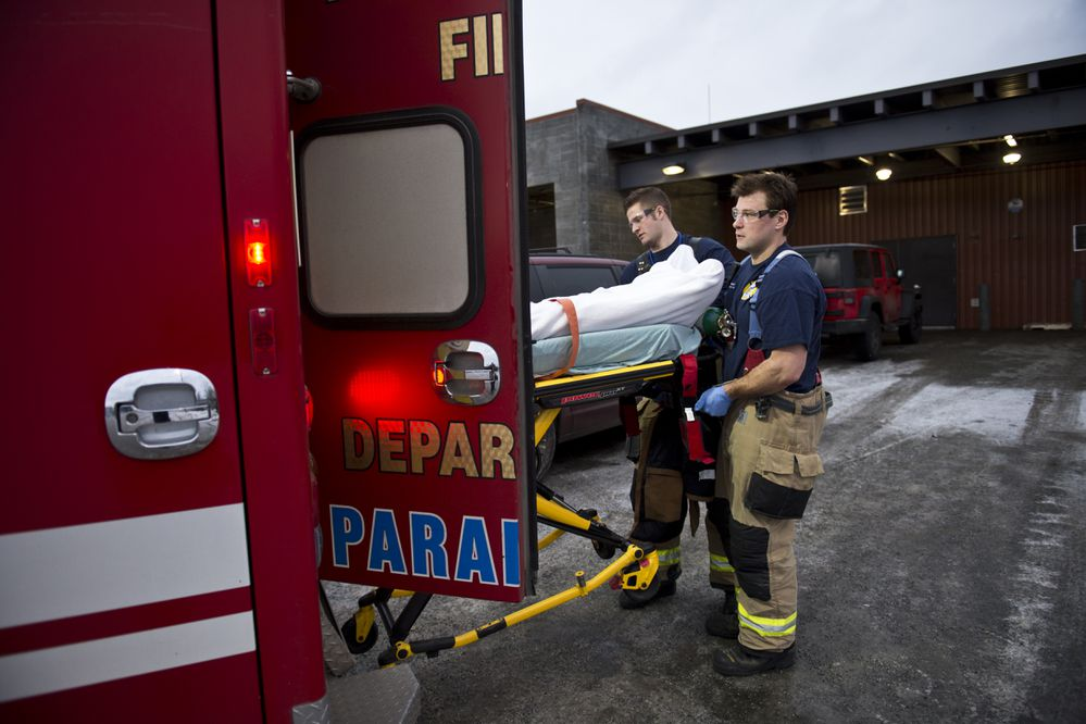 Anchorage firefighters Tyler Belk and Dustin Molle lift a man into an ambulance at Brother Francis Shelter on December 15, 2017. The man complained of heart trouble. (Marc Lester / ADN)