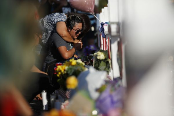 Mayte Santiesteban visits a cross dedicated to her best friend's aunt, who was killed in the weekend shooting, at a makeshift memorial at the site of the mass shooting at a shopping complex, Monday, Aug. 5, 2019, in El Paso, Texas. (AP Photo/John Locher)