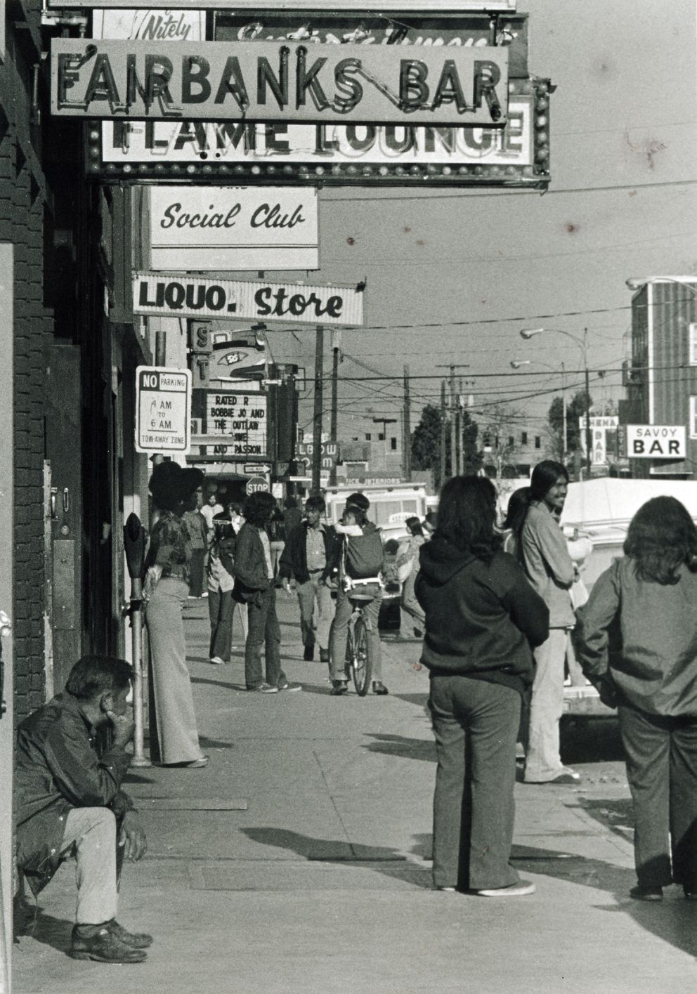 Street scene along Second Avenue in Fairbanks; signs for five bars and a liquor store are visible, including the Fairbanks Bar, Flame Lounge, Social Club, Savoy Bar, and the Chena Bar. (Photo by Paul Helmar / Alaska State Library)