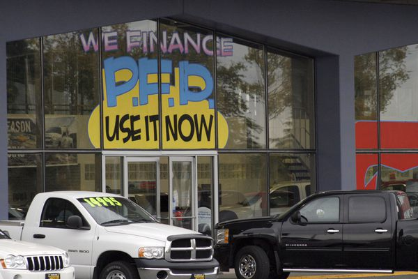 FILE - In this Monday, Sept. 19, 2011 file photo, an auto dealership in Anchorage, Alaska, advertises PFD, or Permanent Fund Dividend, sales. Alaska's unique program of giving residents a check from its oil wealth every year is in jeopardy as the energy-dependent state faces low oil prices and an economy battered by the coronavirus. (AP Photo/Mark Thiessen, File)