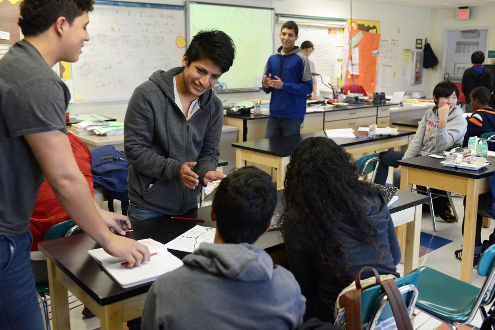 Rosendo Martinez from Mexico, second from left, helps classmates with a lesson in Jessica Stern's class at the Anchorage School District Newcomers' Center on Sept. 30 at Wendler Middle School. (Erik Hill / Alaska Dispatch News)