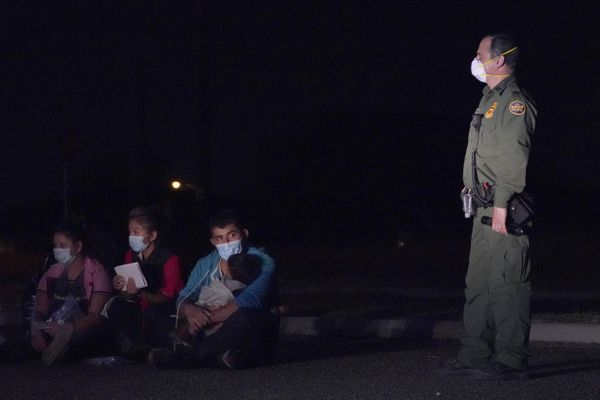 """In this March 24, 2021 photo, a migrant man, center, holds a child as he looks at a U.S. Customs and Border Protection agent at an intake area after crossing the U.S.-Mexico border, early Wednesday, March 24, 2021, in Roma, Texas. The Biden administration said Monday that four families that were separated at the Mexico border during Donald Trump's presidency will be reunited in the United States this week in what Homeland Security Secretary Alejandro Mayorkas calls """"just the beginning"""" of a broader effort. (AP Photo/Julio Cortez)"""