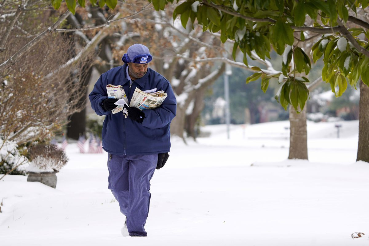 U.S. Postal Services mail carrier RayShawn Riley delivers mail to a snow covered neighborhood after a second winter storm brought more snow and continued freezing temperatures to North Texas on Wednesday, Feb. 17, 2021, in Richardson, Texas. (Smiley N. Pool/The Dallas Morning News via AP)
