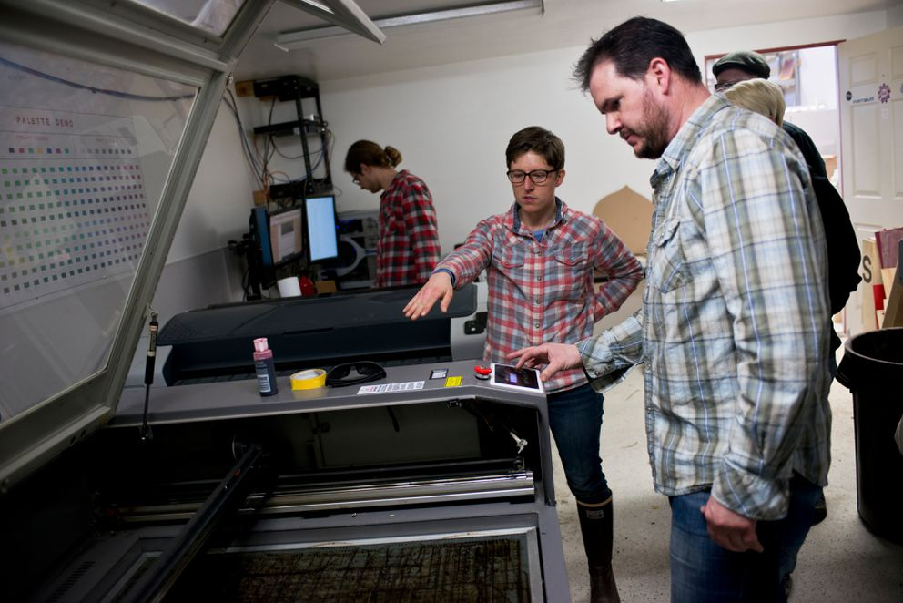 Anchorage MakerSpace instructor Jess Austin, center, talks with Andrew Cater about operating the laser cutter on April 6. Cater came to MakerSpace to make a tap handle for his cold-brew coffee business. (Marc Lester / Alaska Dispatch News)