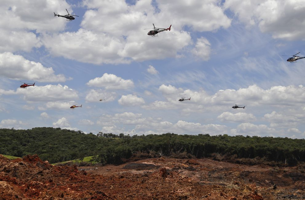 In this Feb. 1, 2019 file photo, helicopters hover over an iron ore mining complex to release thousands of flower petals paying homage to the dozens of victims killed and scores of missing after a mining dam collapsed there one week prior in Brumadinho, Brazil. (AP Photo/Andre Penner, File)