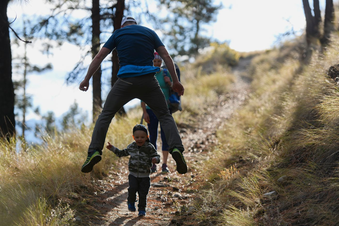 Jeff Ellis leaps over Breck while hiking with Kikkan Randall on the trails near their Penticton, B.C. home on Oct. 9. (Marc Lester / ADN)